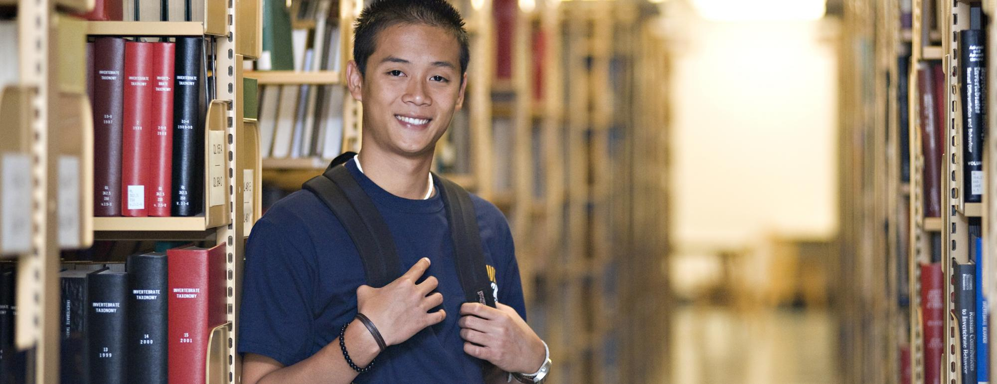 student standing in library stacks